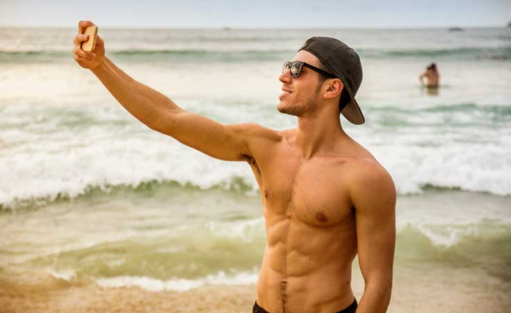 Chico fitness selfie en la playa